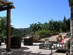 The spacious front terrace of Le Stalle overlooks the terraced garden and hilltop village, Macchie.