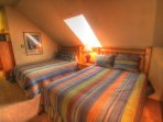 Loft - The loft has 2 queen beds with log headboards and a TV.