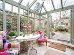 Next to the dining room, the colourful conservatory leads out to the stunning garden