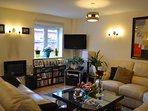 Lounge area, large L-shaped 6 seat sofa + matching 3 seat. Coffee tables, cable TV, DVD and hi-fi.