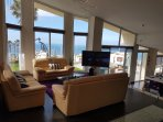 Large open living room with leather sofa, flat screen TV and dream view to the s