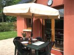 Patio equipped with garden table & chairs, parasol and BBQ.
