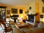 Guests socialise in the cosy sitting room. It's cool in summer and heated by the log fire in winter