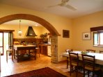 A view of the dining and kitchen spaces separated by the original stone arches.