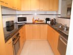 Large well equipped granite top kitchen with pots, plates, cutlery and electrical appliances.