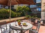 The spacious and sunny terrace looks out onto an interior urban garden