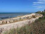 Plage tranquille et chemin piétonnier avec bancs, dunes protégées Piste cyclable