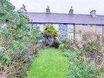 The cottage has a long, enclosed front garden, with lawn and mature trees and shrubs, and garden furniture