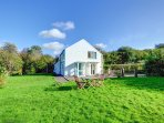 The cottage stands on its own in a large lawned grounds with garden furniture