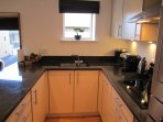 Quality fittings and appliances include granite work surfaces, blender, rice cooker, weighing scales