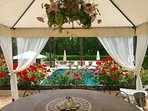Round Stone table for 14, under permanent Pavillion with chandelier overlooking pool