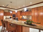 Spacious kitchen with granite counters and travertine floors.