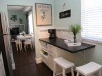 Breakfast bar with microwave,  hidden trash bins = functional kitchen with lots of counter space.