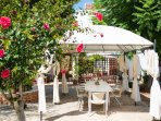 Outdoor dining table with tent surrounded by lovely garden