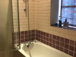 The recently renovated bathroom has bath and good power shower