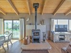 The open living area boasts large windows, ocean-themed decor, and a wood-burning stove.