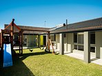 Fully enclosed private front yard with play fort, swings, trampoline and seesaw. Fun for the kids