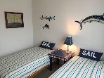 Kids room with twin beds, ceiling fan & balcony