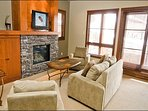Elegant Living Room Features a Stone Fireplace and Flat Screen Cable TV