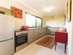 Fully equipped kitchen with oven and gas hob and large fridge.