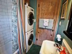 Hall bathroom with a tub/shower combo and stackable washer/dryer