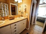 Upper level master bathroom with his & her sinks and a tub/shower combo