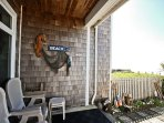 Ocean facing deck and stone patio with patio chairs and spectacular ocean views