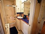 Hall bathroom with a tub/shower combo and a stackable washer/dryer