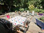 Large back stone patio and deck with patio table, patio chairs and a gas BBQ