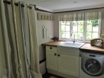 Kitchenette with fridge, microwave, table, chairs, toaster, kettle, washing machine, Butler sink