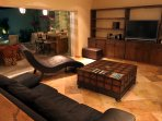 Living room with open sliding pocket doors shows bar/BBQ and pool outside.