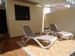Terrasse privative arrière attenante à la chambre. Équipée de meubles de jardin et banne solaire.