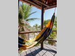 The hammock on north facing side terrace with a peak-a-boo view of the ocean through the palms.