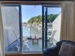 The first floor living room has French windows to a balcony and views of the marina