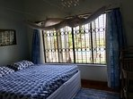 Second bed room with large double bed and mosquito net