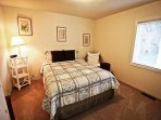 Master bedroom with a Queen bed and wicker chair