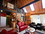 Middle level living room with leather furnishings, wall mounted flat screen cable TV/Blu-Ray DVD player, an electric...