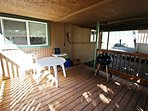 Lower deck area with patio table and chairs, charcoal BBQ and a fenced side yard