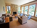 Lower level living room with a river rock gas fireplace, couch, three arm chairs and large picture windows with...