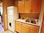 Lower level laundry room with a stackable washer/dryer, sink area and access into the garage