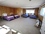 Upper level kids bedroom with four Twin beds, cable TV/VCR, hide-a-bed couch and an arm chair