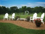 Adirondack chairs by pond with property entrance in background.