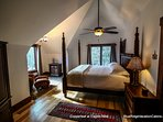 Upstairs bedroom with king bed, sitting area and armoire with television.