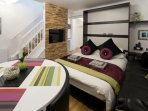Living room with folding wall bed to create second bedroom at night.