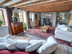 The large sitting room has comfy sofas and is full of character, with beams and a woodburner