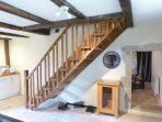 Hand made oak staircase gives access to upstairs bedrooms and bathroom. Exposed oak beams throughout