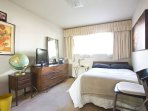 Spacious cozy bed in a large bedroom with a flat screen TV and windows.