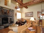 The living room is absolutely gorgeous, with high ceilings crossed by rugged structural beams.