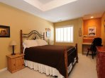 A lower level guest bedroom with a queen bed