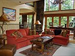 Expansive Windows Frame this Spacious Living Area with Wood Burning Fire Place